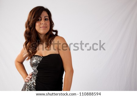 Lovely Caucasian woman in a little black dress, standing with one hand on her hip and with eye contact and a friendly, happy smile for the camera - stock photo