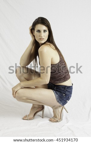 Lovely Caucasian woman in shorts, squatting on the floor and looking thoughtful  - stock photo