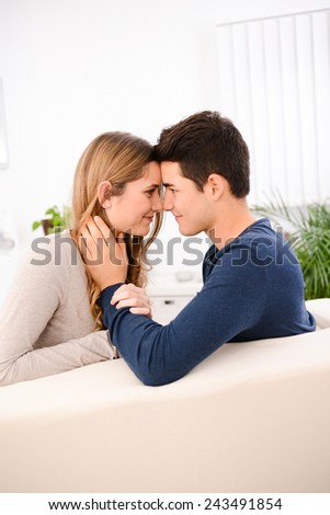lovely cheerful young couple man and woman happy together on sofa at home - stock photo