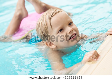 Lovely child doing exercises in water - stock photo