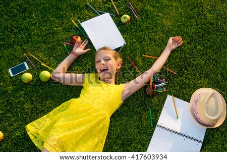 Lovely child is enjoying young life in beautiful green meadow. The best rest for children is to be outdoors. Sincere and pleasant emotion of caucasian young girl. - stock photo