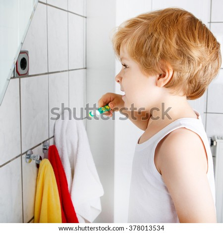 Lovely child learning brushing his teeth in domestic bath. Kid learning how to stay healthy. Health care concept. - stock photo