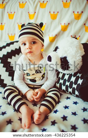 lovely child sits on a sofa with plush panda