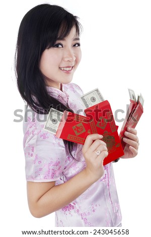 Lovely chinese girl in traditional cheongsam dress holding red envelope with money dollars cash, isolated on white background