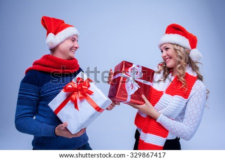 Lovely christmas couple  in Santa Claus hats holding presents on blue background