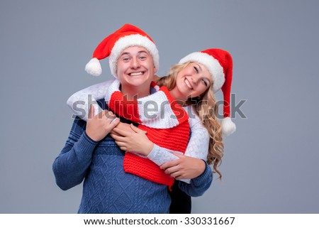 Lovely christmas couple  in Santa Claus hats posing on blue background