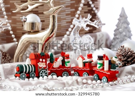Lovely christmas decoration with small red train and pastel ornaments. - stock photo