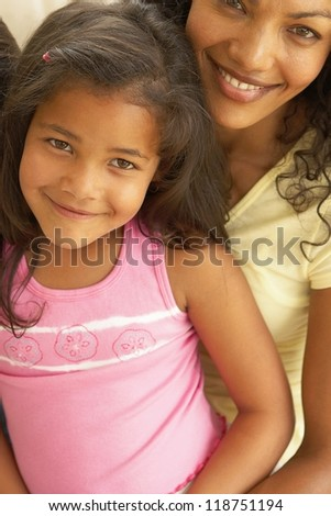 Lovely closeup portrait of a beautiful smiling young woman with her shy little daughter sitting on her lap - stock photo