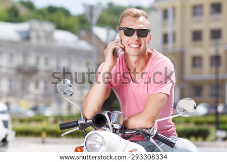Lovely conversation. Handsome young man with glasses sitting on retro scooter and talking per mobile phone. - stock photo