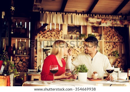 Lovely couple at restaurant enjoy their crucial date, he feeds her with yummy piece of cake.  - stock photo
