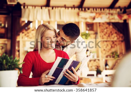 Lovely couple choosing some specialty from menu. While she is sitting he is leaning over her back and kissing her. Shallow depth of field.