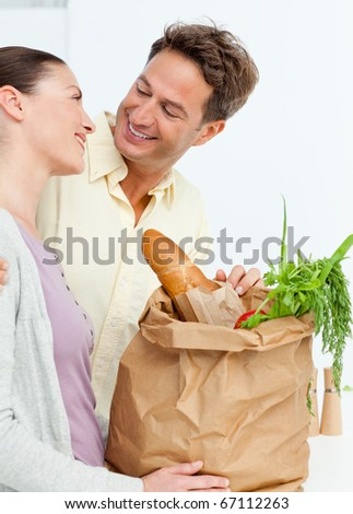 Lovely couple coming back from the market with vegetables in shopping bags