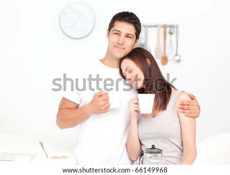 Lovely couple drinking coffee during breakfast in the kitchen - stock photo