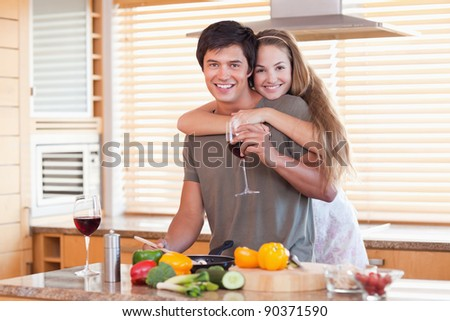 Lovely couple drinking red wine while hugging in their kitchen