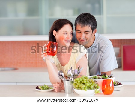 Lovely couple eating and drinking in the kitchen - stock photo