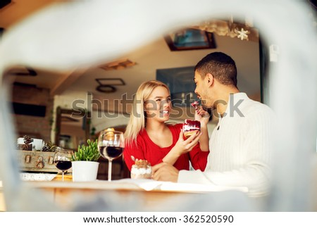Lovely couple enjoying at restaurant, she is feeding him with yummy piece of cake.  - stock photo