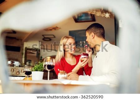 Lovely couple enjoying at restaurant, she is feeding him with yummy piece of cake.  - stock photo