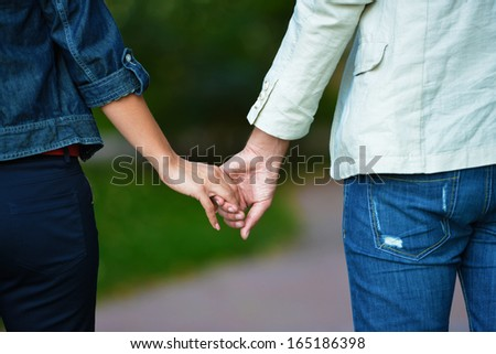 Lovely couple holding hands in the middle of summer
