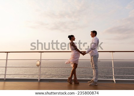 lovely couple holding hands on a cruise ship - stock photo