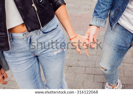 Lovely couple holding hands together,Two beautiful hipsters standing outdoor on the street in autumn urban background. Pretty blonde woman in short dress having fun in Europe,romantic date