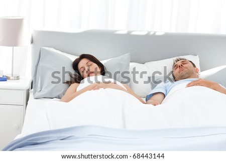 Lovely couple holding their hands while sleeping on their bed at home