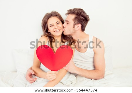 Lovely couple in love holding red paper heart in bed and kissing - stock photo