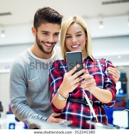 Lovely couple is at store and they are looking for a new mobile. They are smiling and looking at smart phone. Shallow depth of field. - stock photo