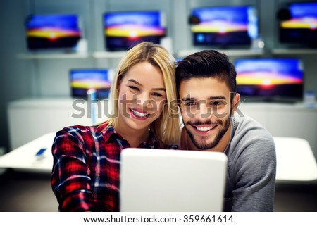 Lovely couple is at store and they are looking for a new tablet. They are taking selfie and smiling. Shallow depth of field. - stock photo