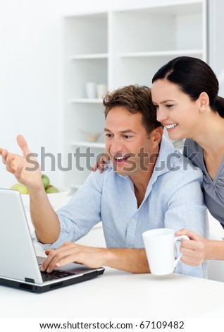 Lovely couple laughing while watching something on the laptop screen in the kitchen
