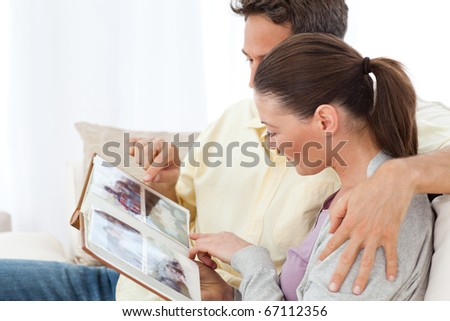 Lovely couple looking at pictures on a photo album on the sofa at home