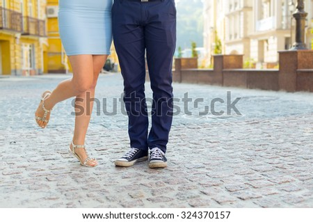 Lovely couple.  Man and woman. Feet, close-up. Couples foots stay at the street under sunlight. Close-up of legs of the kissing couple. Young man and woman walking together. Kissing couple.