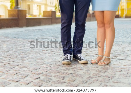 Lovely couple. Man and woman. Feet, close-up. Couples foots stay at the street under sunlight. Man and a woman walking down the street together. Tourist walk the journey - the concept of a weekend.