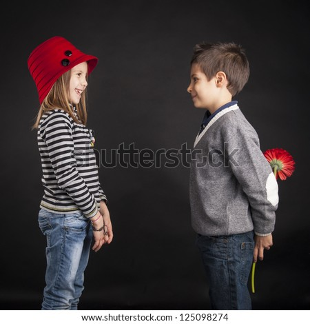 Lovely couple of kids. Boy offering flower on black background. Valentines day concept. - stock photo