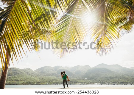 lovely couple on the beach with palms and mountain view with sunflare in vietnam - stock photo