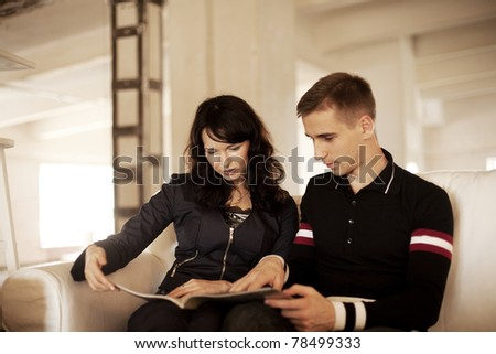 Lovely couple reading a book together on the sofa at home - stock photo