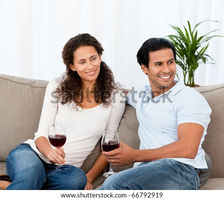 Lovely couple relaxing with red wine in the living room - stock photo