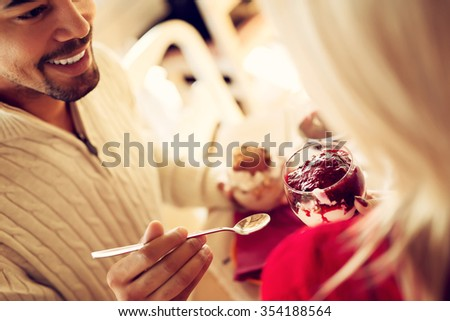 Lovely couple sharing mixed ice cream and enjoying their precious moments. Shallow depth of field, selective focus at ice cream cup. - stock photo