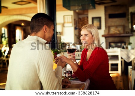 Lovely couple sitting at restaurant and holding hands.She is holding wine glass and looking at him. Shallow depth of field. - stock photo