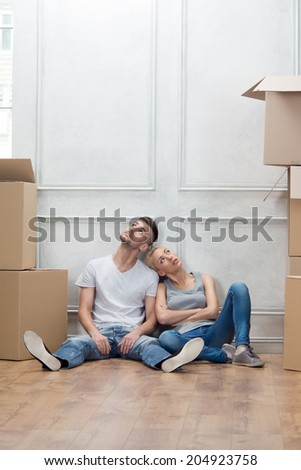 Lovely couple sitting on the floor and leaning against the wall tired because of hard removal