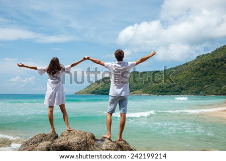 lovely couple standing in rocks above the sea and holding hands up - stock photo