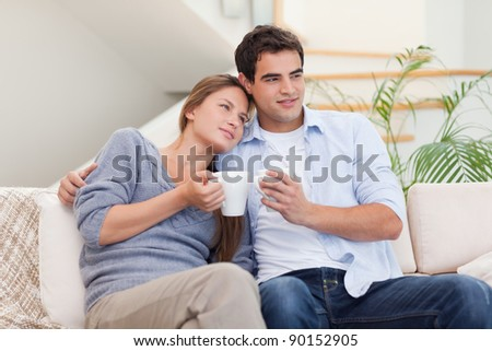 Lovely couple watching TV while drinking coffee in their living room - stock photo