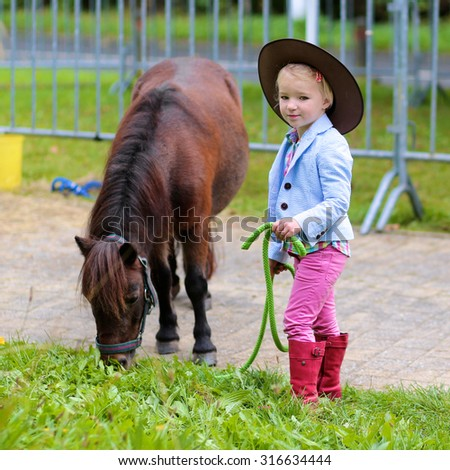 Lovely cowgirl feeding with grass little pony horse in the farm. Pretty preschooler girl wearing cowboy hat playing with animals outdoors on sunny day. - stock photo