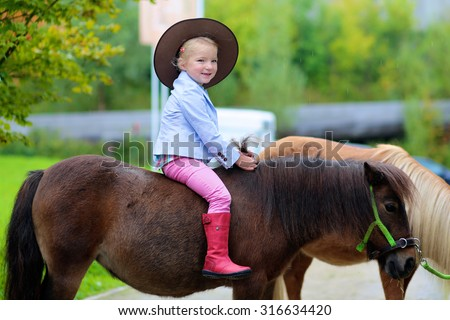 Lovely cowgirl riding little pony horse in the farm. Pretty preschooler girl wearing cowboy hat playing with animals outdoors on sunny day. - stock photo