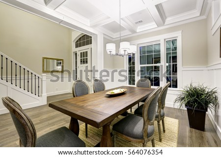 Lovely Craftsman Style Dining Room With Coffered Cealing Over Wooden Dining  Table Surrounded By Grey Chairs
