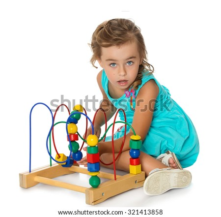 Lovely, cute little girl in Montessori kindergarten played with educational games. Girl wearing a blue dress , She looks directly into the camera with open mouth-Isolated on white background - stock photo