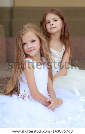 Lovely cute little girls with long hair in long white dresses sitting on the steps - stock photo