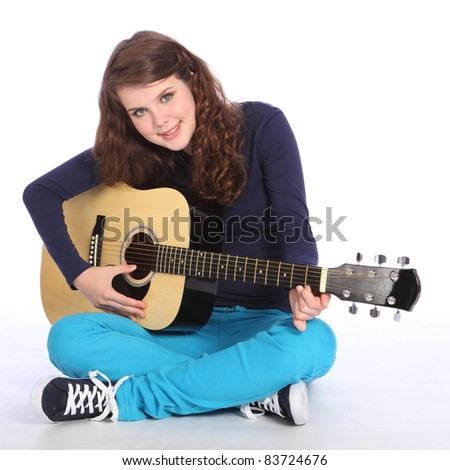 Lovely cute smile from pretty teenager girl with bright blue eyes, sitting on floor playing music on acoustic guitar. She is wearing bright blue trousers and navy top.