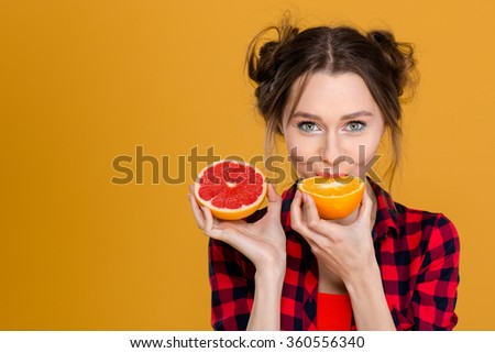 Lovely cute young woman in plaid shirt tasting orange and grapefruit over yellow background - stock photo