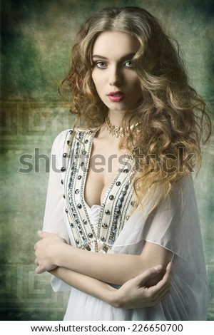 lovely dame with antique style and golden jewellery posing with curly long hair and looking in camera  - stock photo