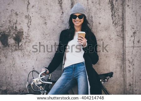 Lovely day. Beautiful young woman in sunglasses holding coffee cup and looking at camera with smile while standing against concrete wall outdoors  - stock photo